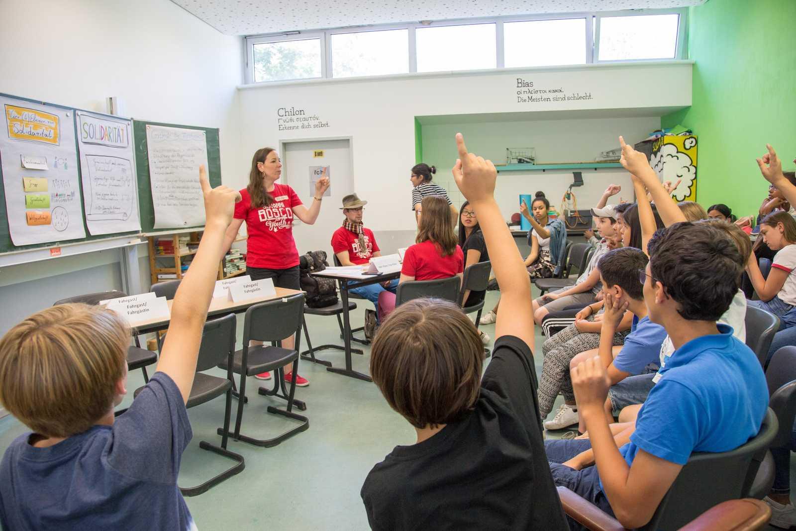mehrere Schüler zeigen auf